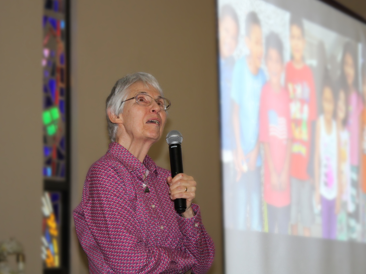 Sister Patricia Weidman speaking into a microphone