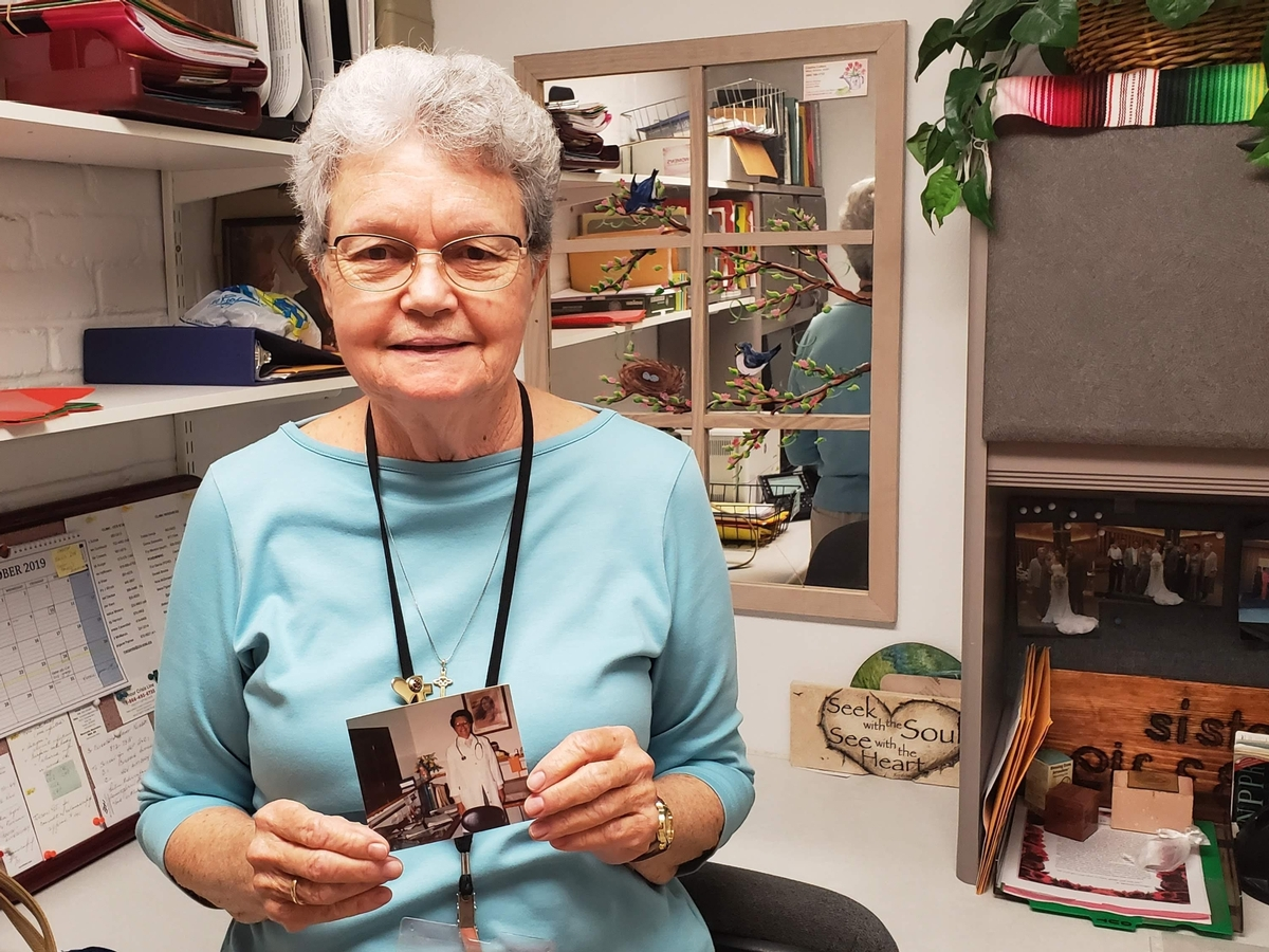 Sister Eileen in her office with a photo of her from 1985