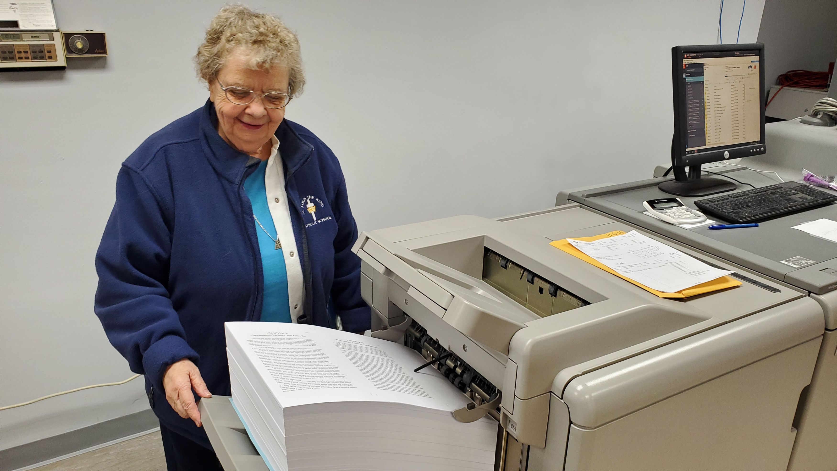 Sister Jean watches the book in print