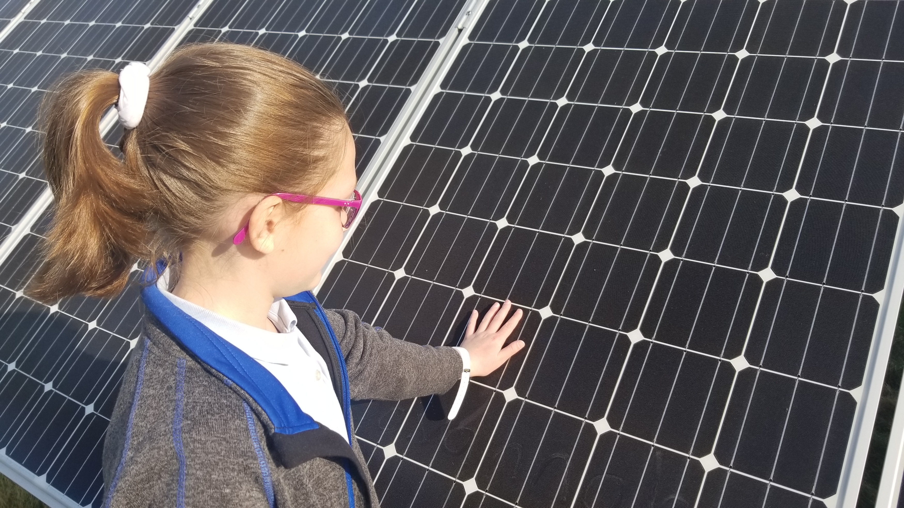 Girl with hand on solar panel